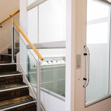 Aritco 7000 lift installed by Easy Access Lifts in Western Australia. Image shows white and glass lift shaft installed into the corner of a staircase.
